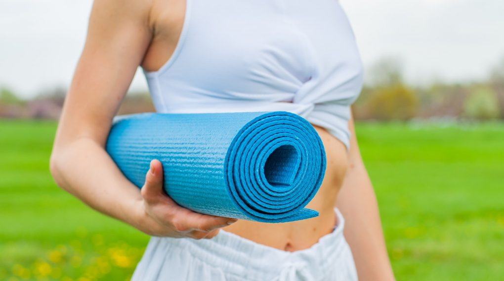 woman standing and holding blue gym mat_how to clean gym mats at home